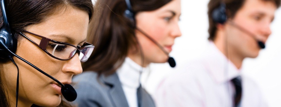 Customer service team working in headsets woman in front.