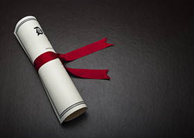 Diploma with a red ribbon on a black leather background