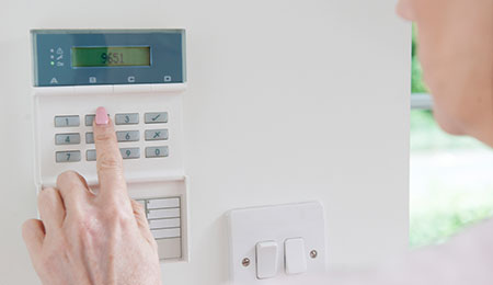 person putting in code to their alarm system