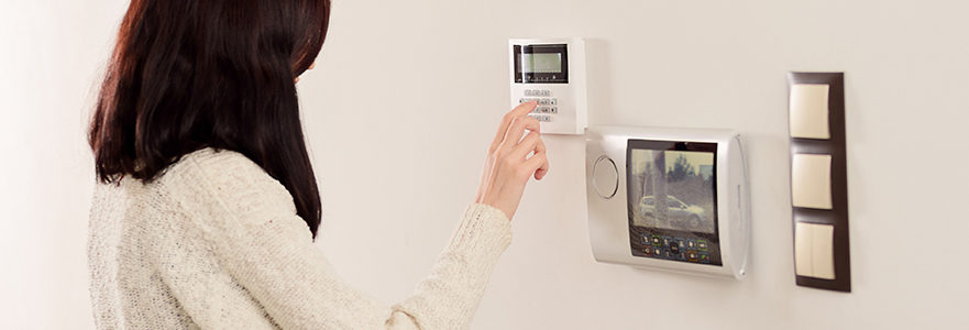 Woman Using Home Security Monitoring System To View Outside